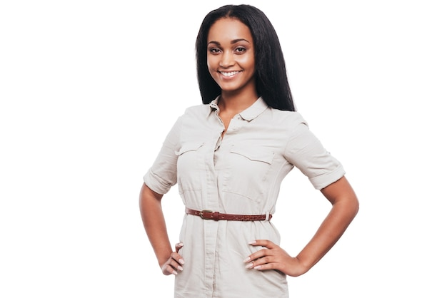 Beauté confiante. souriante jeune femme africaine tenant les mains sur les hanches et regardant la caméra en se tenant debout sur fond blanc