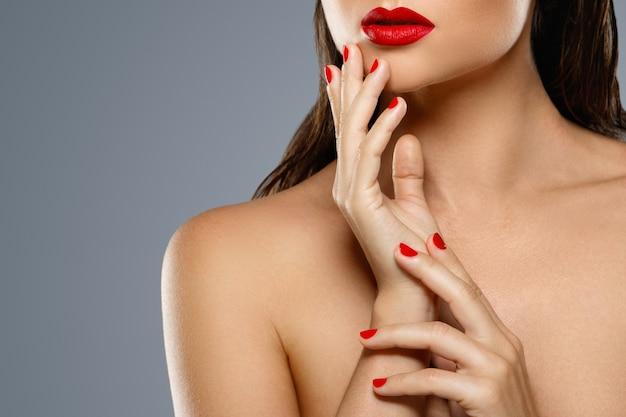 Beauté et cosmétique. bouche et ongles féminins avec manucure rouge et rouge à lèvres.
