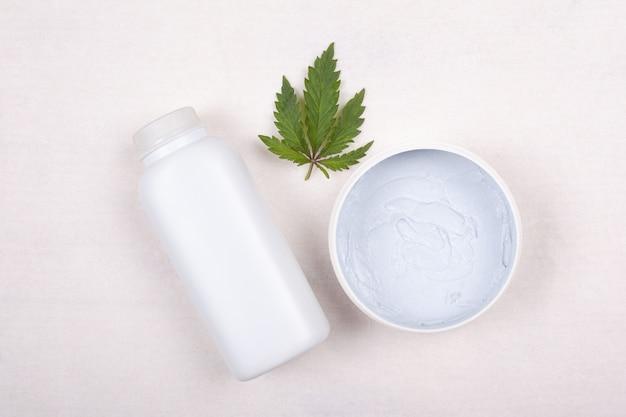 Beauté, ð¡ cosmétiques avec de la marijuana. ð¡ream et feuille de cannabis sur fond blanc.