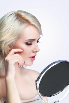 Beauté du visage, portrait de jeune femme sexy avec une peau saine et fraîche à la recherche dans le miroir à l'intérieur,