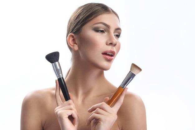 Beauté éclatante. belle jeune femme avec du maquillage professionnel appliqué posant avec deux pinceaux de maquillage en détournant les yeux fond de beauté cosmétiques mode style artiste styliste profession concept de l'industrie
