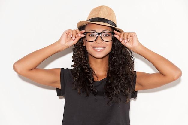 Beauté élégante. belle jeune femme africaine à lunettes et chapeau funky ajustant ses lunettes et souriant à la caméra en se tenant debout sur fond blanc