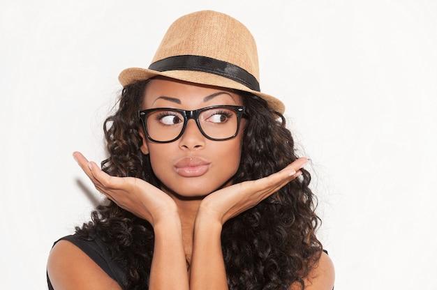Beauté élégante. portrait d'une belle jeune femme africaine à lunettes et chapeau funky faisant des gestes et regardant loin en se tenant debout sur fond blanc