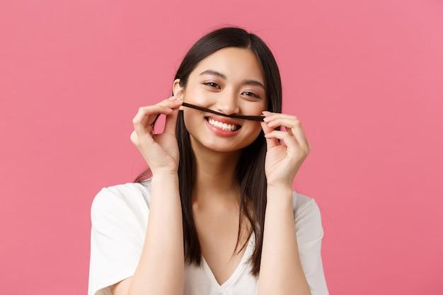Beauté, émotions des gens et concept de loisirs d'été. fille asiatique drôle et stupide tenant une mèche de cheveux sur la bouche pour imiter la moustache, souriante sans soucis, debout sur fond rose.