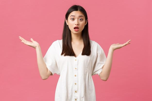 Beauté, émotions des gens et concept de loisirs d'été. fille asiatique troublée et confuse en robe blanche debout sans aucune idée, a besoin d'aide, haussant les mains les mains écartées sur le côté et regard nerveux