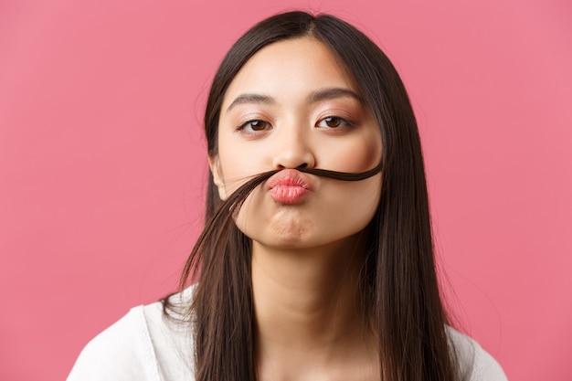 Beauté, émotions des gens et concept de loisirs d'été. gros plan d'une fille asiatique idiote drôle et ennuyée faisant une fausse moustache avec une mèche de cheveux sur la lèvre, une caméra de regard ludique, fond rose