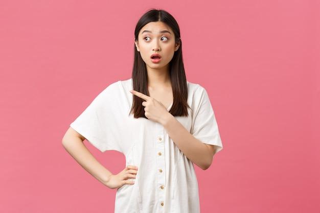 Beauté, émotions des gens et concept de loisirs et de vacances d'été. fille asiatique confuse à la perplexité et incertaine, pointant le doigt vers la gauche avec un visage surpris intrigué, fond rose.