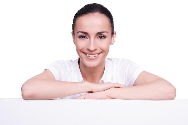 Beauté avec espace de copie. belle jeune femme se penchant à l'espace de copie et souriant tout en se tenant isolé sur blanc