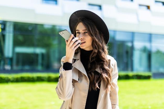 Beauté étudiante parlant avec système mains libres smartphone tout en tenant un dossier sur le campus de l'université.