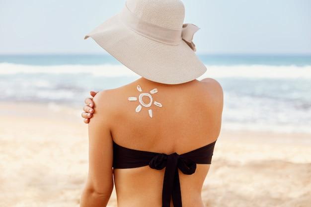 Beauté femme appliquant la crème solaire sur l'épaule bronzée.