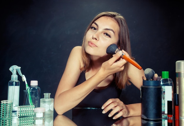 Beauté femme appliquant le maquillage. belle fille regardant dans le miroir et appliquant des cosmétiques avec un gros pinceau. modèle caucasien au studio