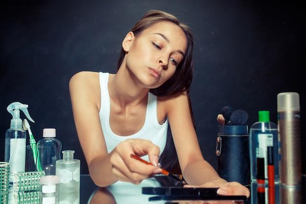 Beauté femme appliquant le maquillage. belle fille regardant dans le miroir et appliquant des cosmétiques avec un pinceau. matin, maquillage et concept d'émotions humaines. modèle caucasien au studio