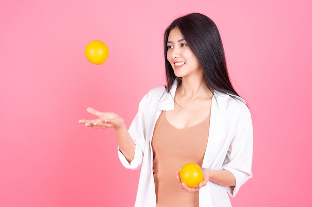 Beauté femme asiatique jolie fille sentir heureux holdind fruit orange pour une bonne santé sur fond rose