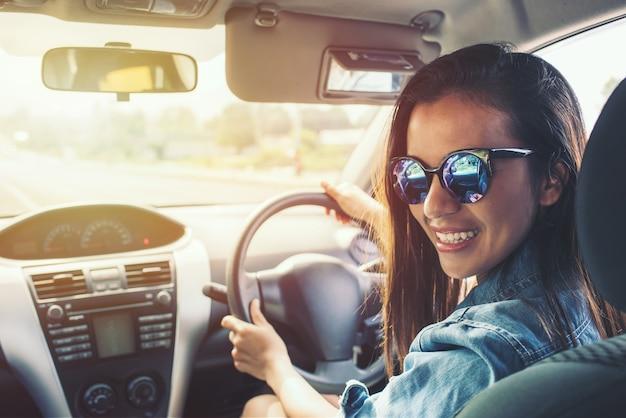 Beauté femme asiatique sourire avec veste en jean bleu lunettes de soleil voiture au moment du coucher du soleil.