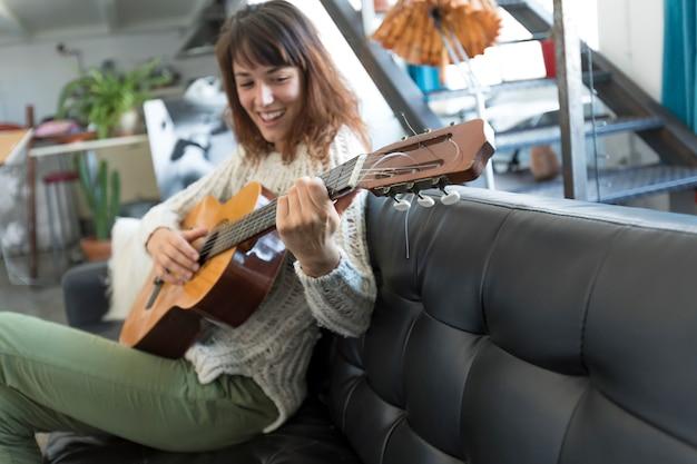 Beauté femme assise sur un dofa et jouant de la guitare