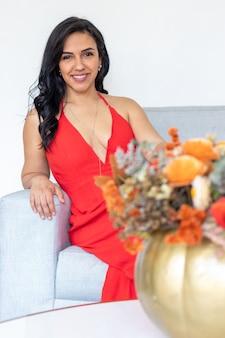 Beauté femme brune aux cheveux longs et robe rouge assis avec un arrangement de fleurs à l'intérieur d'une citrouille peinte de couleur pour célébrer un halloween différent
