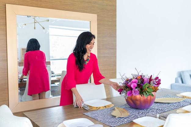 Beauté femme brune aux cheveux longs et robe rouge décore la table avec un arrangement de fleurs à l'intérieur d'une citrouille peinte de couleur pour célébrer un halloween différent