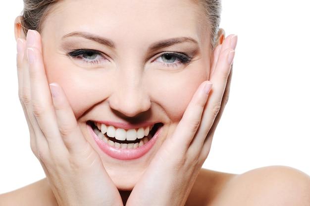 Beauté femme heureuse avec les mains sur son visage propre sur fond blanc