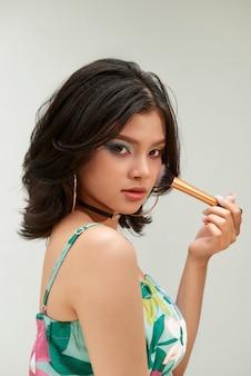 Beauté femme avec des pinceaux de maquillage. maquillage naturel pour fille modèle asiatique avec fard à paupières arc-en-ciel. relooking.