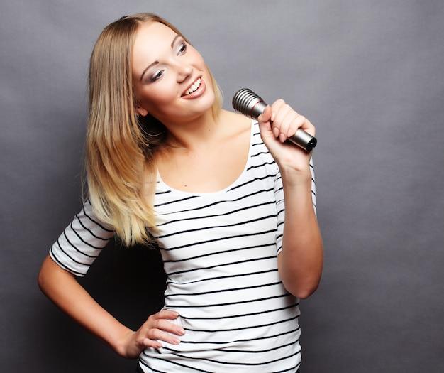 Beauté femme portant un t-shirt avec microphone sur arr.plans gris