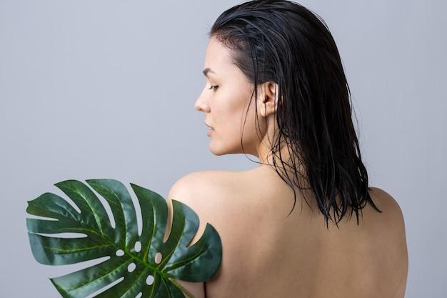 Beauté femme avec portrait de feuille de palmier vert naturel. mode, beauté, maquillage, cosmétiques.