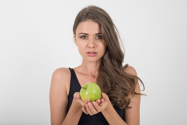 Beauté femme tenant une pomme verte alors qu'elle est isolée sur blanc