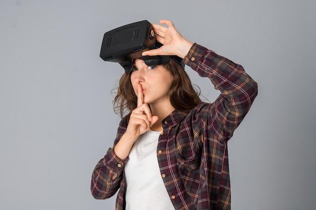 Beauté femme testant des lunettes de réalité virtuelle en studio sur mur gris