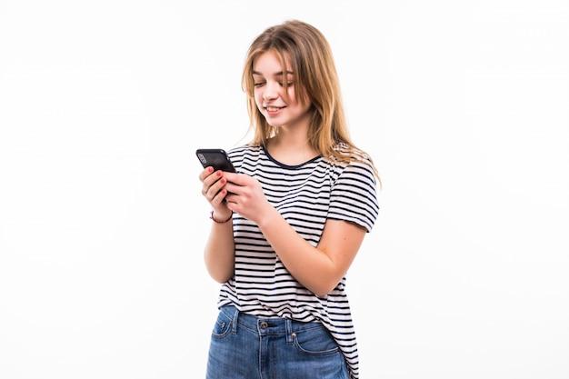 Beauté femme utilisant et lisant un téléphone intelligent isolé sur un mur blanc