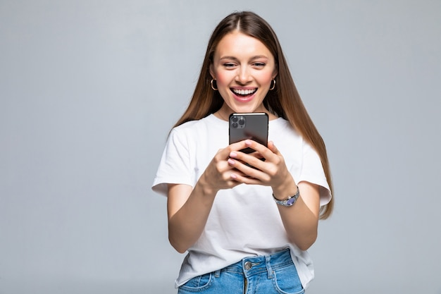 Beauté femme utilisant et lisant un téléphone intelligent isolé