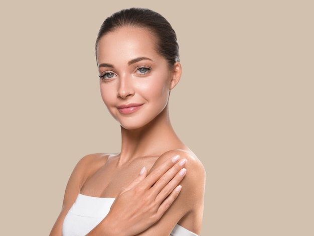 Beauté femme visage peau saine spa propre. beaux cheveux de jeune mannequin. couleur de fond marron