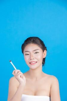 La beauté des femmes avec des images parfaites de la santé de sa peau toucher son visage et sourire comme un spa pour prendre soin de sa peau bleu