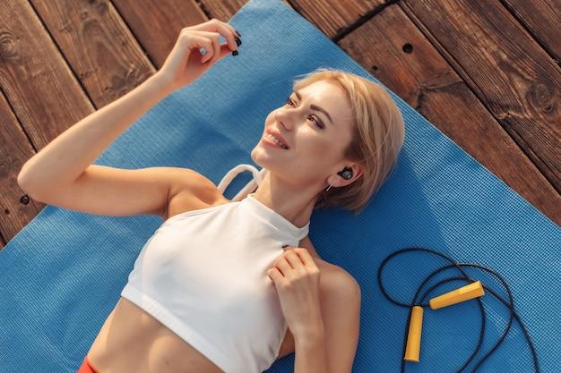 Beauté fitness femme se trouve sur un tapis et écoute de la musique sur des écouteurs en plein air