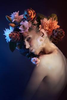 La beauté fleurit le visage d'une femme avec une double exposition. portrait d'une fille néon et couleur, maquillage professionnel, dos nu d'une femme, fleurs dans la tête