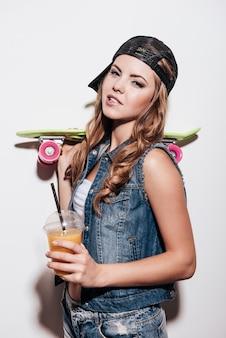 Beauté fraîche. belle jeune femme tenant une planche à roulettes colorée et une tasse de jus avec de la paille en se tenant debout sur fond blanc