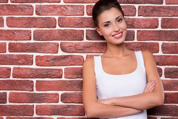 Beauté géniale. portrait de la belle jeune femme aux cheveux courts gardant les bras croisés et souriant tout en se tenant contre le mur de briques