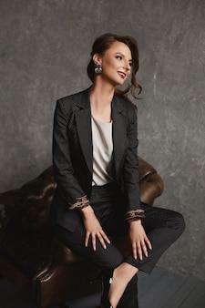 Beauté incroyable une fille modèle magnifique avec un maquillage et une coiffure parfaits en costume élégant posant dans le fauteuil vintage