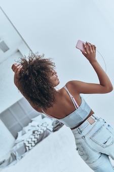 Beauté insouciante. vue arrière d'une jolie jeune femme africaine écoutant de la musique et souriant tout en dansant dans la chambre à la maison