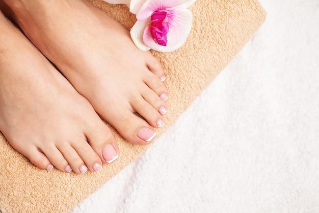 Beauté jambes minces féminines après thérapie spa sur fond blanc.