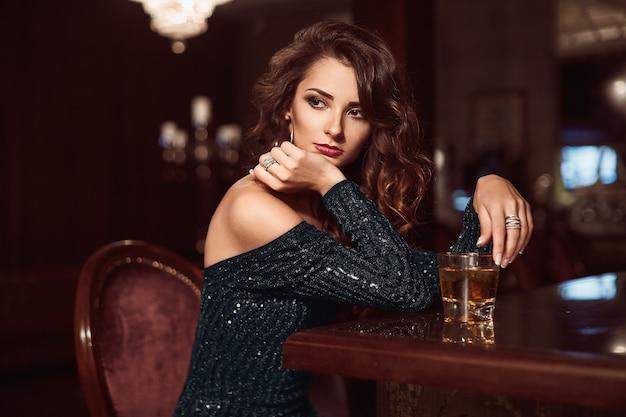 Beauté jeune femme brune assise au bar