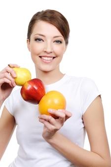 Beauté de la jeune femme en riant tenant des fruits
