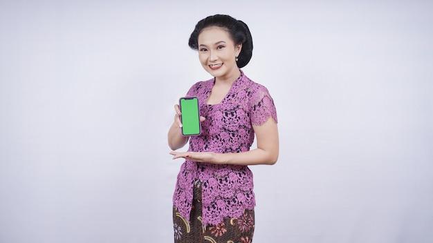 Beauté en kebaya souriant montrant l'écran du smartphone isolé sur fond blanc