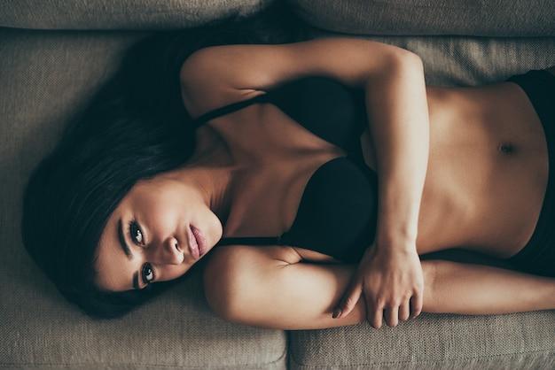 Beauté en lingerie. vue de dessus de la belle jeune femme métisse en lingerie noire regardant la caméra en position couchée sur le canapé