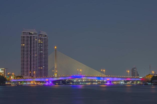 La beauté des lumières colorées sur le pont pinklao et des voitures roulant la nuit sur la rivière chao phraya