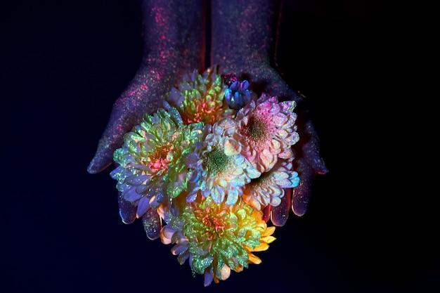 Beauté des mains d'une femme en lumière ultraviolette avec des fleurs dans les paumes