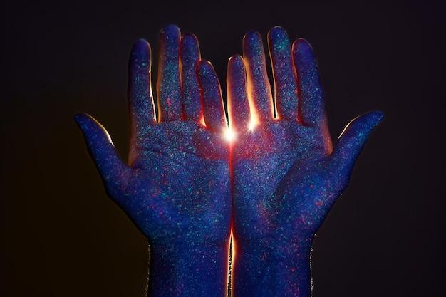 Beauté des mains à la lumière ultraviolette en gouttes de peinture colorée. lumière à travers les paumes de vos mains, dieu et la religion. cosmétiques pour les mains