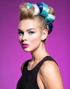 Beauté mannequin fille aux cheveux teints colorés. fille avec maquillage et coiffure bleus. maquillage bleu. studio.