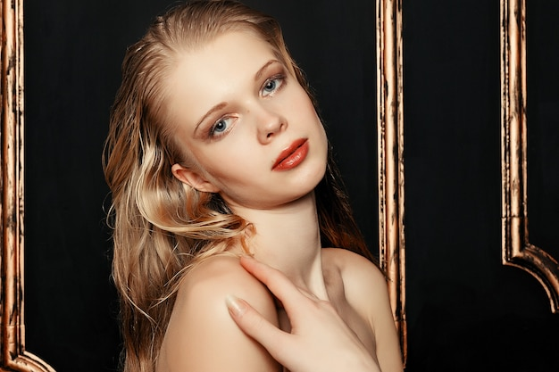 Beauté mannequin fille maquillage naturel cheveux mouillés sur fond d'or noir dans des tons chauds. portrait de jeune femme avec le maquillage de mode