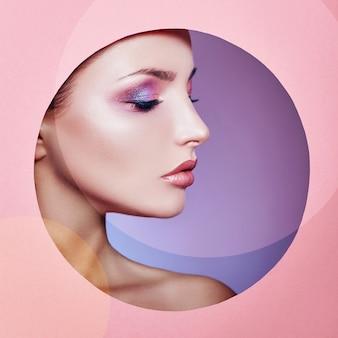 Beauté maquillage cosmétiques nature mode femme dans un cercle de trous ronds en papier rose, copie espace publicitaire. maquillage professionnel peau parfaite et rouge à lèvres brillant.