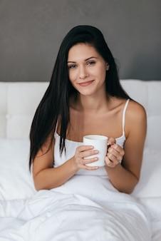 Beauté le matin, magnifique jeune femme souriante et tenant une tasse
