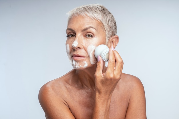 Beauté mature. jolie femme âgée impatiente de faire la procédure de nettoyage du matin